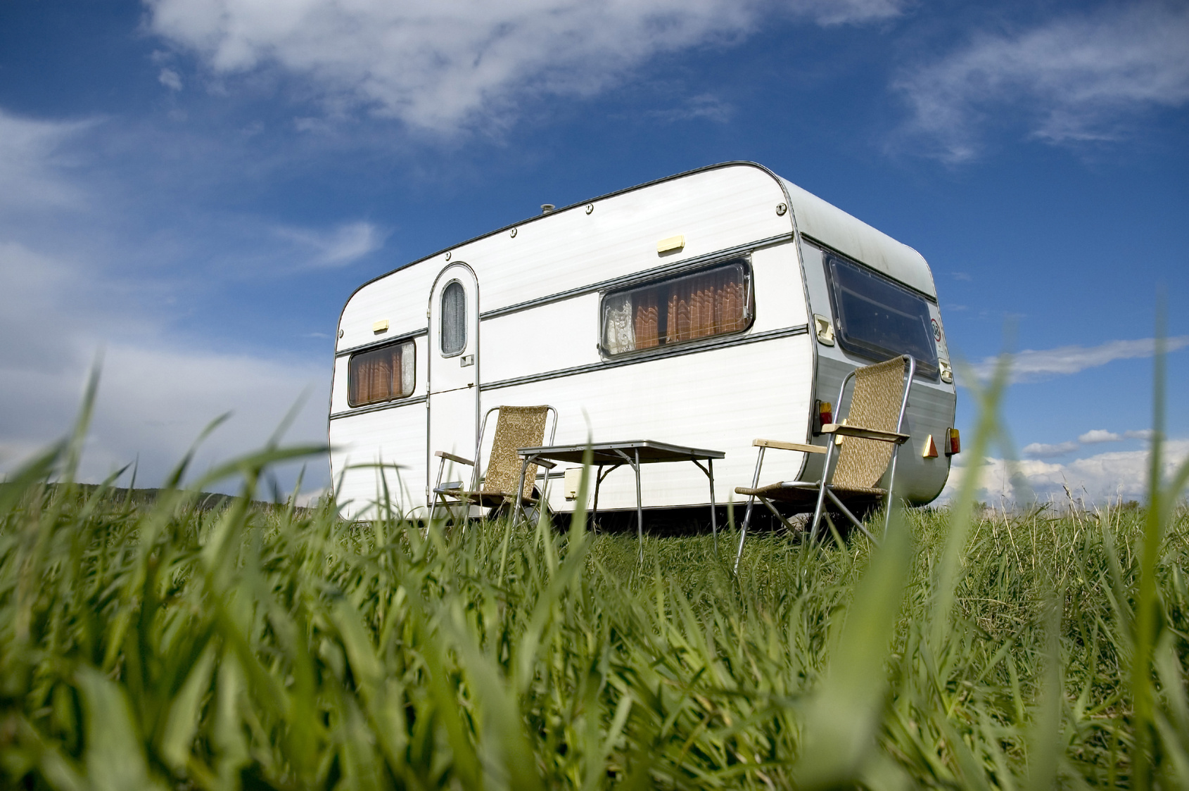Caravan in a field with chairs